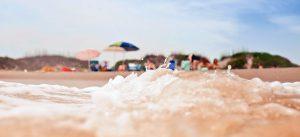 A photo of a small wave hitting the sand on the beach with a family in beach chairs in the background.