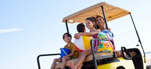 A family on the beach, sitting in a golf cart.