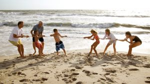 A photo of a group of people playing tug of war on the beach.